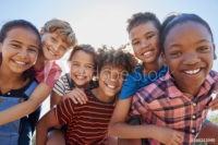 Six pre-teen friends piggybacking in a park, close up portrait