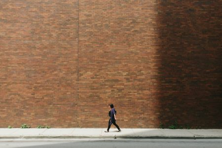 woman in black shirt walking on sidewalk near brown concrete wall partition
